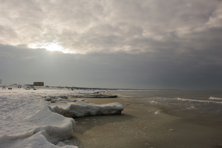 Beautiful winter landscape with snowy breakwater and ice, Baltic Sea