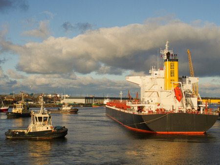 Tugboat assisting bulk cargo ship to leave the pier