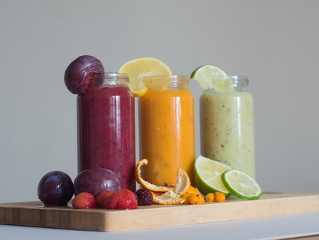 Fresh raspberry, banana, spinach and orange drinks on wooden table. Detox diet concept.