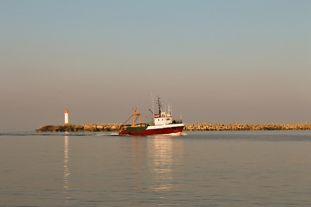 Small red fishing boat entering the port