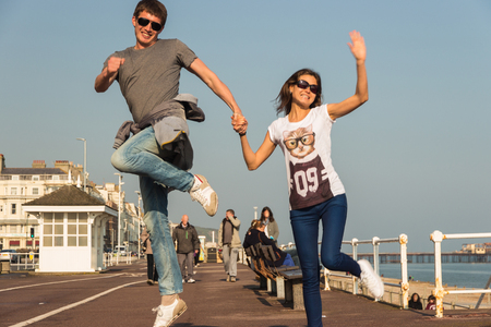 Young couple holding hands and jumping. Stock Photo