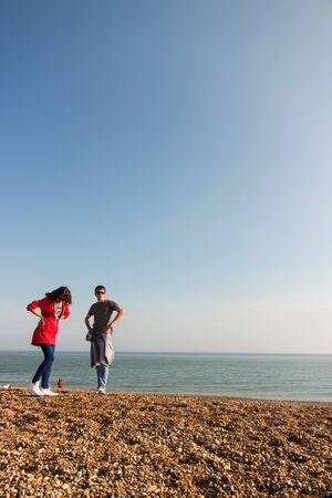Young fashionable couple standing at the beach in UK
