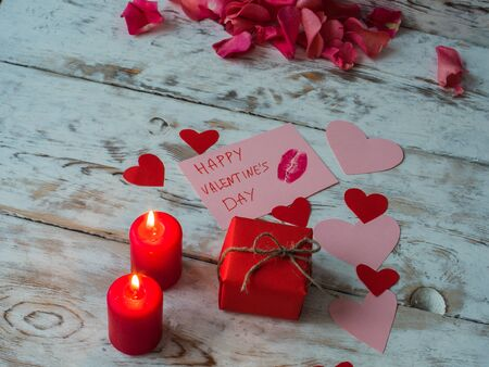St Valentines decor on wooden background, red candles with red gift and hearts from craft paper. Stock Photo