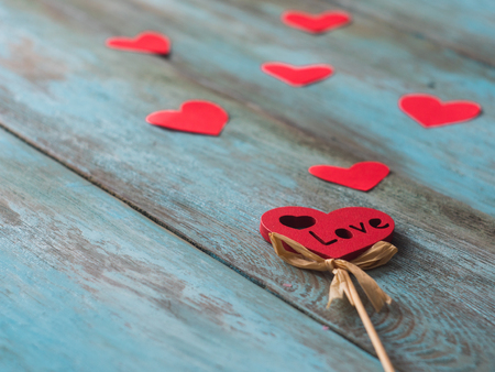 Valentines Day background with hearts on old wooden table, side view