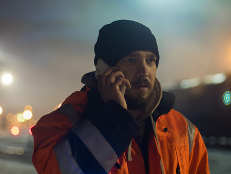 Worker talking by smartphone bokeh light in bacground. Concept of night shift Imagens