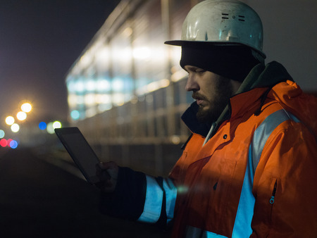 Portrait of young engineer working on tablet during hignt otdoors in helmet and reflective jacket Reklamní fotografie