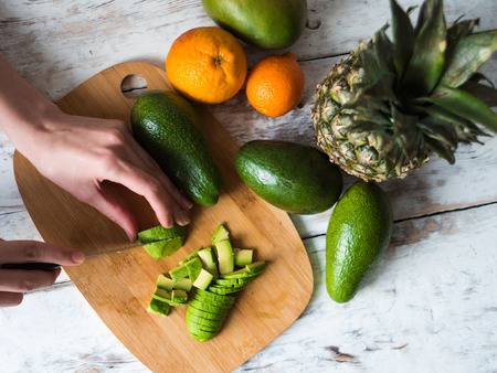 women s health: female hands cooking with avocado at table in home kitchen