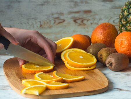 pinnaple: Close up woman hands cutting fresh orange with knife and wooden chopping board.