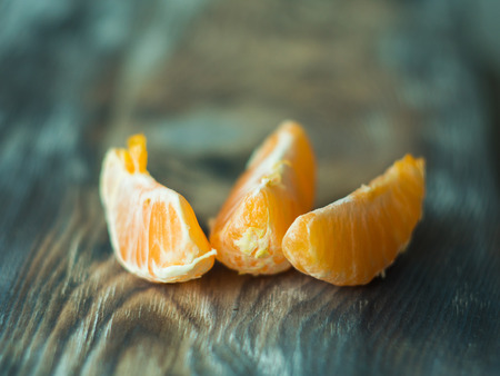 Fresh tangerine slices on wooden table, close up Stock Photo