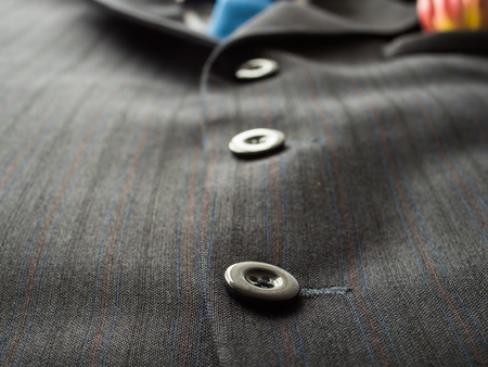 Black buttons on a mans suit background with blue tie., close up . Stock Photo