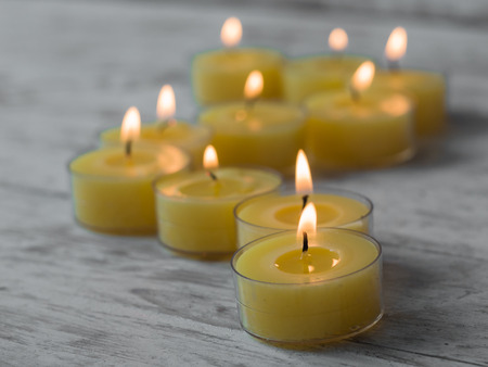 Yellow candles on a white wooden background, shallow depth of field. Spa treatment concpet.