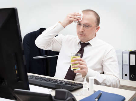 Sick man in a white business shirt and red tie working in office on a desktop computer, have got a headache, holds glass with medicine and wipes forehead with a napkin, close up