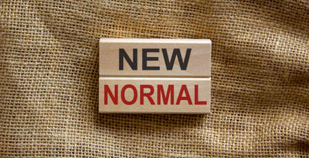 Wooden blocks form the text 'new normal' on beautiful canvas background.