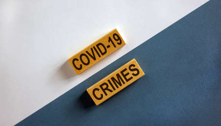 'Covid-19 crimes' words on wooden blocks. Business concept. Beautiful white and blue background.
