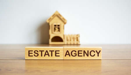 Blocks form the words estate agency in front of a miniature house. Banco de Imagens