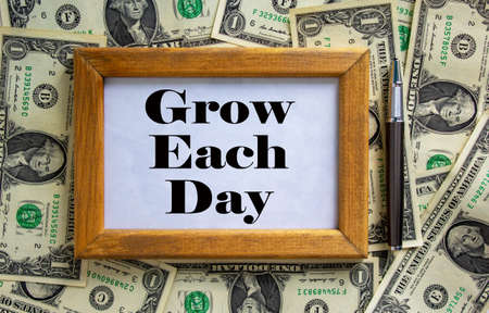 Wooden picture frame with inscription 'grow each day' on beautiful background from dollar bills and metalic pen. Concept.