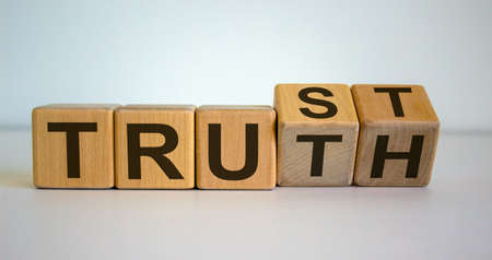 Wooden cubes and changes the word 'Truth' to 'Trust'. Beautiful white background.