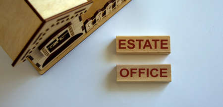 Wooden blocks form the words 'estate office' near miniature house.