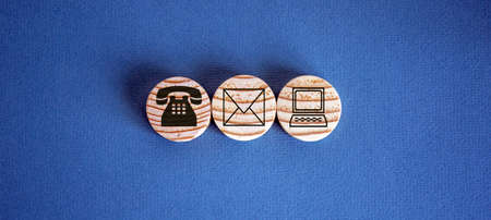 Three wooden cut circles with contact and information icons on them. Stock fotó