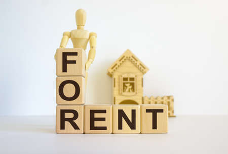 Cubes form the words 'for rent' in front of a miniature house. Warm light. Wooden model of human.