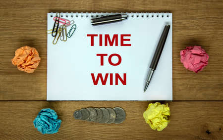 White note with inscription 'time to win' on beautiful wooden table, colored paper, coins, pen, cap and colored paper clips. Business concept.