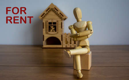 Wooden model of a sitting man in front of a miniature house. For rent inscription.