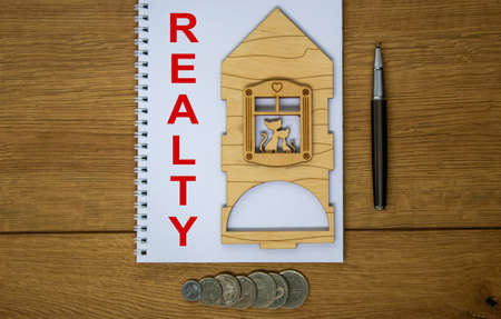 White note with inscription 'realty' on beautiful wooden table, metalic pen, coins and miniature wooden house. Business concept.