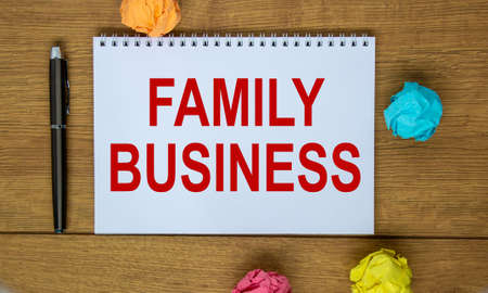 White note with inscription 'family business' on beautiful wooden table, colored paper, metalic pen. Business concept.