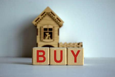 Cubes form the word 'buy' in front of a miniature house.