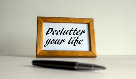 Wooden picture frame with inscription 'declutter your life' on beautiful white fon. Pen on the table. Banque d'images