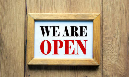 Wooden picture frame with inscription 'we are open' on beautiful wooden background. Concept.
