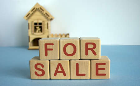 Cubes form the words for sale in front of a miniature house. Banco de Imagens