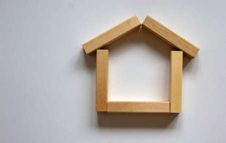 Wooden model of house from blocks. Place for your text. White background.