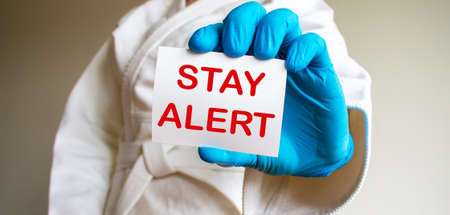 A young strong man in a white kimono for sambo, jiu jitsu and other martial arts with a blue medical gloves. Card with words 'stay alert'. COVID-19 Pandemic Coronavirus and medical concept.
