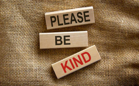 Wooden blocks form the text 'please be kind' on beautiful canvas background. 版權商用圖片