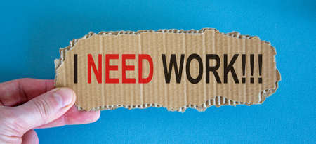 Words 'i need work' on the piece of cardboard between fingers. Beautiful blue background, copy space.