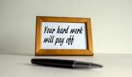 Wooden picture frame with inscription 'your hard work will pay off' on beautiful white background. Pen on the table.