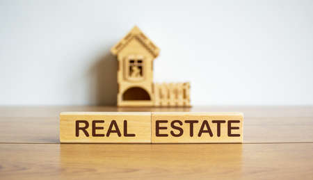 Blocks form the words real estate in front of a miniature house.