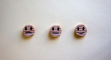 Various emoticons made of wooden circles and hand drawn lines of a mouth. Over yellow background in a conceptual image of quality and feedback.