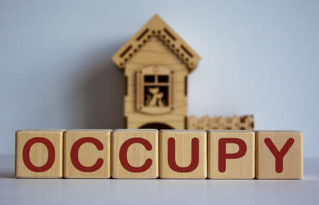 Cubes form the word 'occupy' in front of a miniature house.