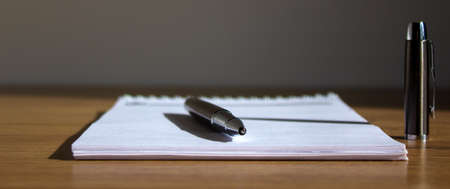 Notebook and pen on beautiful wooden table. Concept background. Warm sunlight. Banque d'images