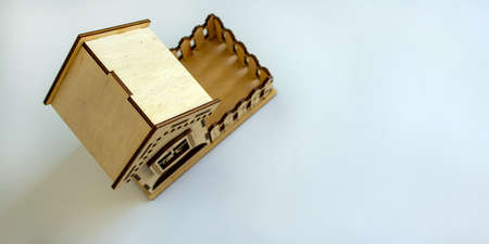 Wooden miniature house. Beautiful white background, copy space.