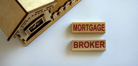 Wooden block form the words 'mortgage broker' near miniature house. Beautiful white background, copy space. Stock Photo