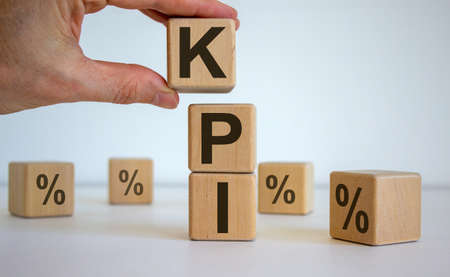 Male hand placing a cube with letter K on top of a other cubes. KPI word. Beautiful white background. Concept of successful business processes.
