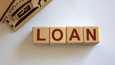 Wooden cubes form the word 'loan' near miniature house. Stock Photo
