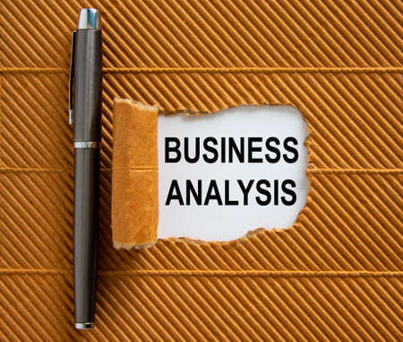 The text 'business analysis' appearing behind torn brown paper. Beautiful metalic pen.