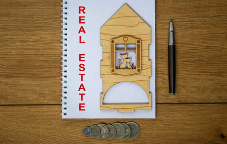 White note with inscription 'real estate' on beautiful wooden table, metalic pen, coins and miniature wooden house. Business concept.