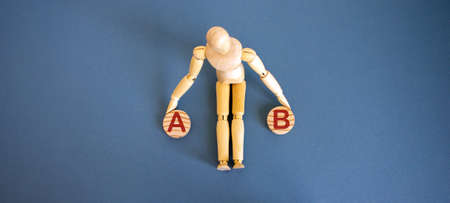 Wooden model of a man seats near 2 small wooden circles with leters a and b. Business concept.
