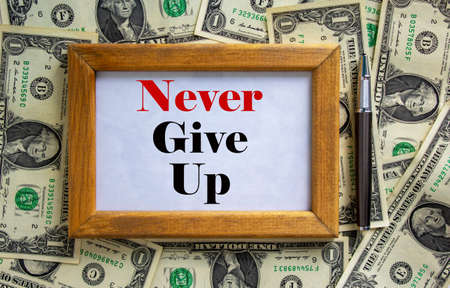 Wooden picture frame with inscription 'never give up' on beautiful background from dollar bills and metalic pen. Concept. Banque d'images