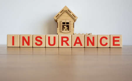 Cubes form the word insurance in front of a miniature house.
